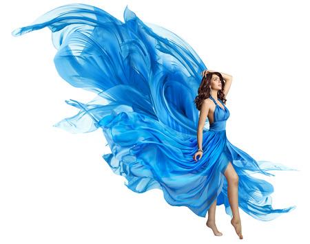 Mujer volando vestido azul, elegante modelo de moda en vestido ondeante en blanco, mosca de tela de arte y aleteo en el viento Foto de archivo