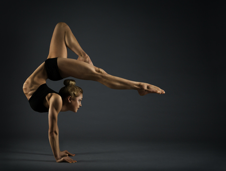 Flexible Woman Circus Gymnast, Gymnastics Hand Stand, Young Acrobat Standing on Hands, Yoga Headstand Backbend Exercise over black background