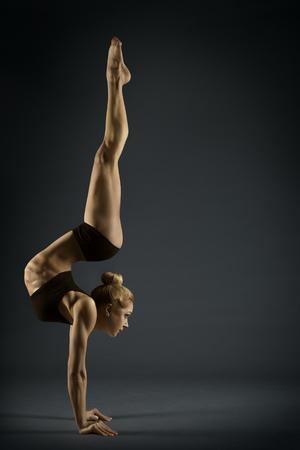 Yoga Handstand Gymnastics, Woman Acrobat in Hand Stand Pose, Strong Girl Gymnast Flexible Body Balance on Hands over Black Background