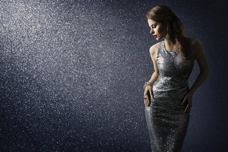 Vestido plateado, modelo posando en brillante vestido sexy, elegante retrato de belleza de mujer sobre fondo de destellos de iluminación