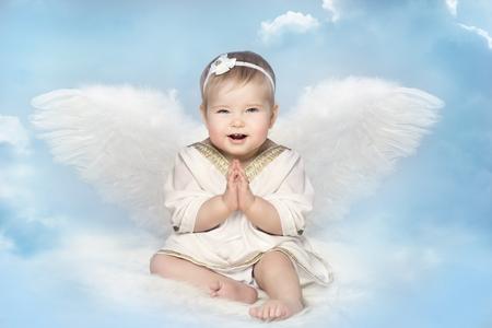 Angel Baby con Amur Wings, Kid Cupid Sitting on Blur Sky, Happy Girl Child Portrait