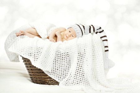 Newborn Baby Lying in Basket, New Born Child in Woolen Knitted Hat over White Background