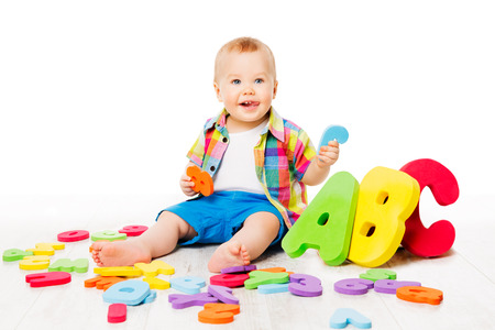 Baby Alphabet Toys, Child Playing Colorful ABC Letters, Kid sitting over White background, Early Education concept Stock Photo