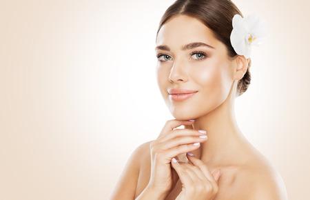 Belleza de mujer, Cuidado de la piel facial y maquillaje natural, Chica con flor de orquídea en cabello lacio, Maquillaje hermoso y cuidado de la piel Foto de archivo