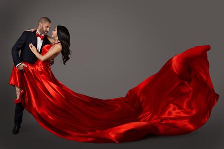 Pareja de baile, mujer en vestido rojo y hombre elegante en traje, tela ondeando volando Foto de archivo