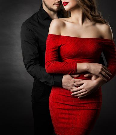 Pareja de belleza de moda, mujer joven en sexy vestido rojo y hombre abrazando en el amor