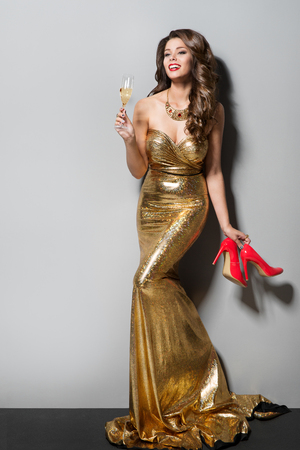 Fashion Model in Long Gold Dress Dancing and Drinking, Happy Young Elegant Woman ith High Heel Shoes