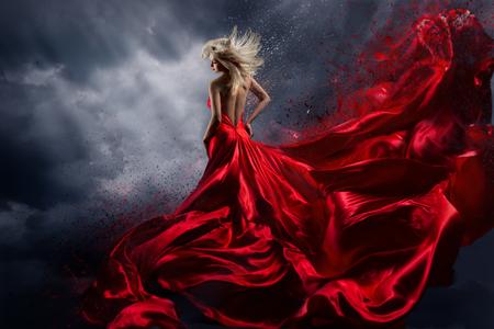 Mujer en vestido rojo baila sobre el cielo de tormenta, vestido de tela ondeante volando como salpicaduras