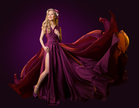 Woman Flying Purple Dress, Fashion Model Dancing in Long Waving Gown, Fluttering Fabric on Wind Stock Photo