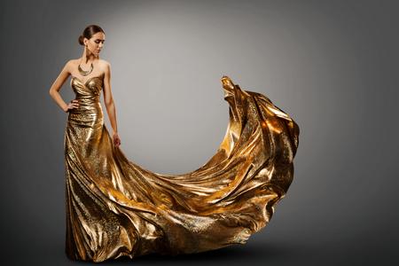 Vestido dorado de mujer, modelo de moda en vestido largo ondeando, retrato de estudio de belleza de niña