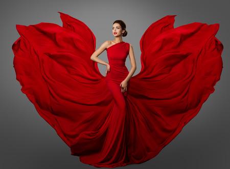 Frau rotes Kleid, Model in langen, schwingenden Seidenkleidflügeln, fliegender, flatternder Stoff