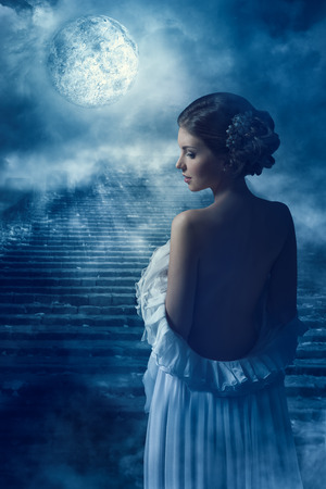 Fantasy Woman Back Rear View Portrait in Moon light, Fairy Mystic Girl in Night looking over shoulder Stock Photo