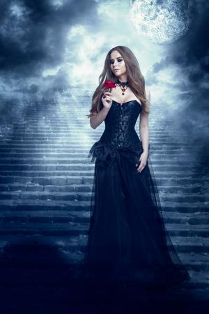 Fantasy Woman in Black Dress Smelling Rose Flower, Mystic Girl in Long Retro Gothic Gown Banco de Imagens