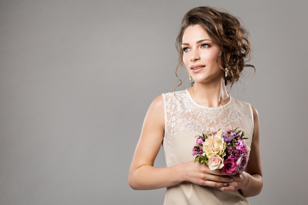 Fashion Models Beauty Portrait with Flowers Bouquet, Beautiful Woman Bridal Makeup and Hairstyle, Girl studio shot on gray background