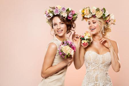 Fashion Models Flowers Hairstyle Beauty Portrait, Two Happy Women Studio Shot with Flower Wreath and Rose Bouquet Banco de Imagens