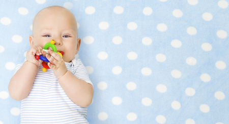 Baby Boy with Teether Toy In Mouth over Blue Background, Happy Infant Kid Boy in Bodysuit Lying on Blue Blanket, Top View Archivio Fotografico
