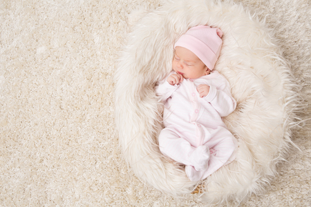 Śpiące noworodek, noworodek śpi na białym futerku, piękny portret studyjny niemowlęcia, jeden miesiąc
