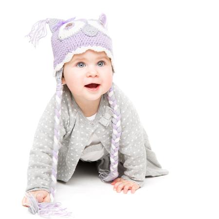 Bambino che gattona su sfondo bianco, bambino felice con cappello di lana, bellissimo ritratto di ragazza di un anno