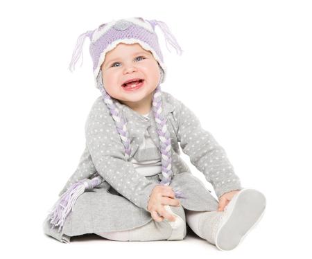 Baby sitter su sfondo bianco, bambino felice in cappello di lana, bellissimo ritratto di ragazza di un anno