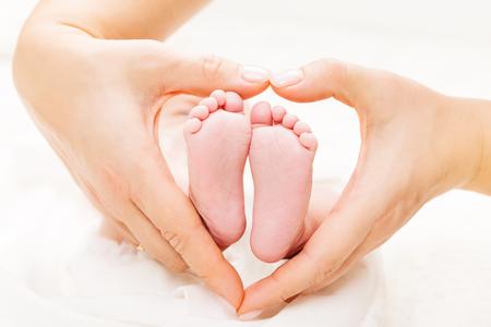Pasgeboren babyvoeten in moederhanden Hart, moeder en pasgeboren kind Voet, liefde en gezondheidszorg Stockfoto