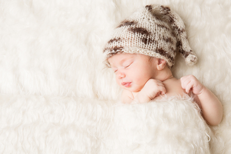 Newborn, baby sleeping in white bed, beautiful new born infant portrait in hat