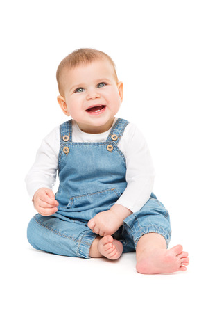 Happy Baby, Infant Kid Sitting on white background, Smiling One year old Child in Jeans Banco de Imagens