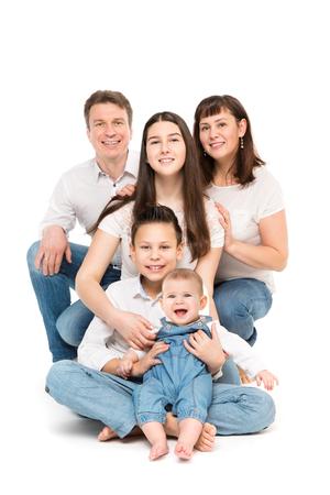 Retrato de estudio familiar, padres felices y tres hijos con bebé sobre fondo blanco.