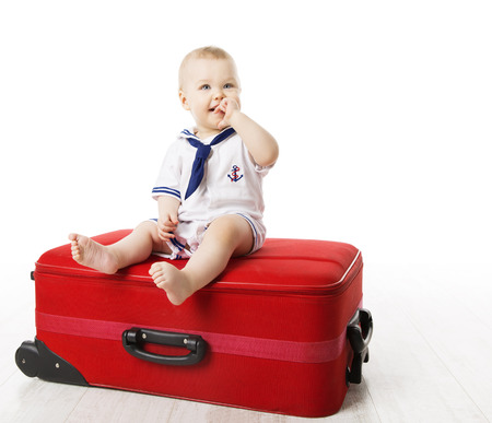 Kid on Travel Suitcase, Baby Boy Sitting on Red Luggage, One Year Old Child isolated over White background