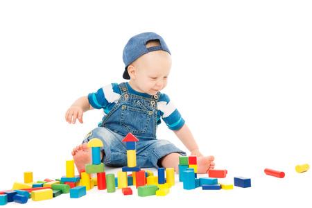 Bebé jugando bloques de juguetes, juego de niños coloridos ladrillos de construcción, niño de un año en blanco
