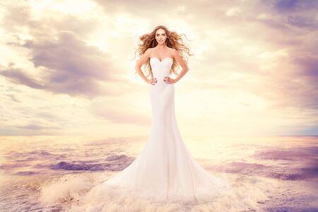 Fashion Model in Sea Waves, Beautiful Woman in Elegant White Dress Hairstyle Waving on Wind, Art Portrait