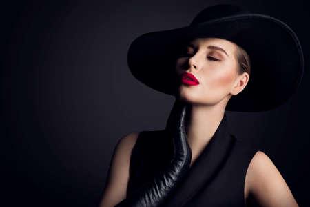 Woman Beauty in wide brim Hat, Elegant Fashion Model Retro Portrait on Black Banco de Imagens
