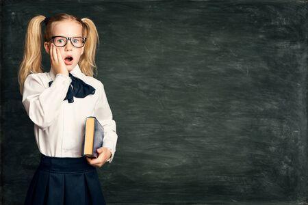 Amazed Child Girl on School Blackboard Background, Astonished Kid in Glasses over Black Chalk Board Фото со стока