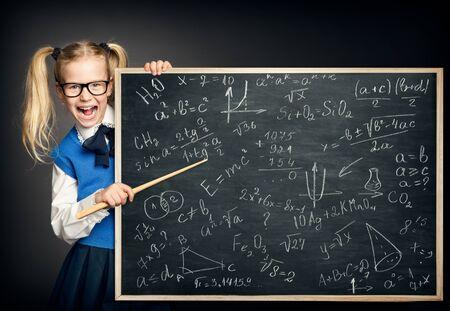 Child Girl Pointing School Blackboard with Mathematics Formulas, Amazed Kid Pupil as Teacher Foto de archivo