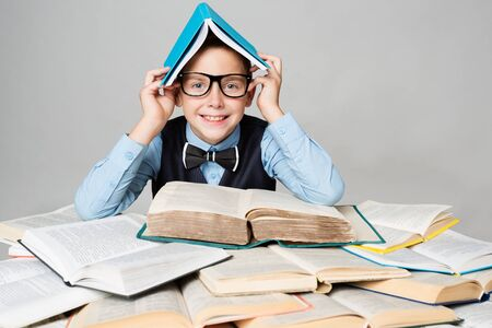 Happy Child Reading Many Books with Book on Head, Funny School Boy in Glasses, Easy Education