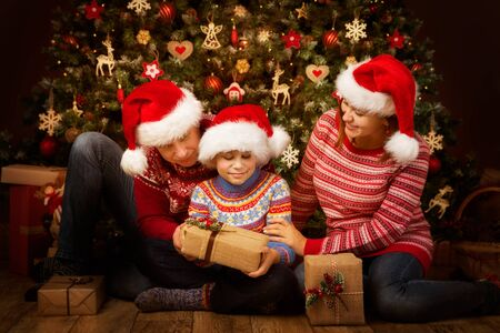 Christmas Family Open Present Gift front of Xmas Tree, Happy Parents with Child in Santa Claus Hats Stock Photo