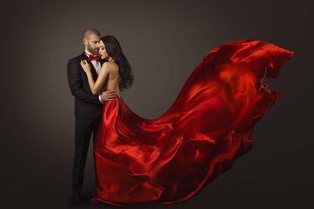 Retrato de belleza de pareja, hermosa mujer bailando en vestido rojo y hombre elegante, tela ondeando en el viento