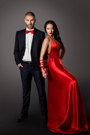 Fashion Couple, Woman Red Dress and Man in Black Suit, Hands Bounded, Love Concept