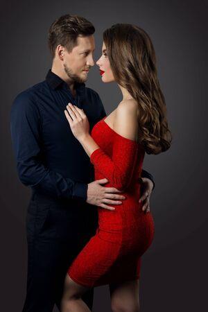 Retrato de belleza de pareja, mujer hermosa en vestido rojo abrazando a hombre elegante, cara a cara Foto de archivo