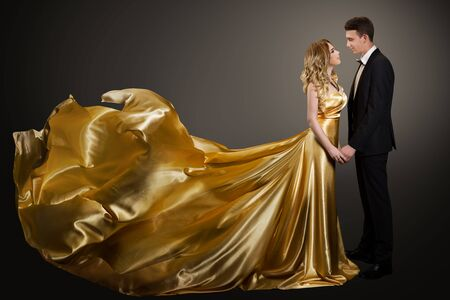 Couple, Beautiful Woman in Golden Silk Dress and Elegant Man in Suit, Gown Fluttering on Wind Stock Photo