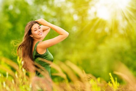Outdoor-Porträt der glücklichen jungen Frau in der Natur. Attraktives Mädchen im sonnigen grünen Sommerpark