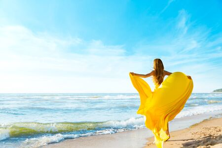 Woman on Sunny Sea Beach in Yellow Fluttering Dress, Fashion Model Back Rear View, Silk Cloth Waving on Wind