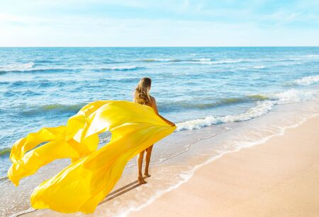 Fashion Model walking Sea Beach in Yellow Fluttering Dress, Woman Back Rear View, Silk Cloth Waving on Wind