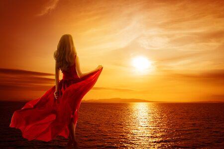 Woman on Sea Beach looking to Sunset Sky, Girl in Red Dress Fluttering on Wind, Rear back view Reklamní fotografie