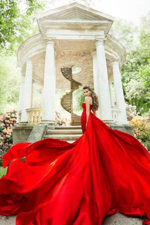 Fashion Model Waving Long Fluttering Red Dress, Woman in Garden, Old White Alcove in Flowers, Outdoor Beauty Portrait
