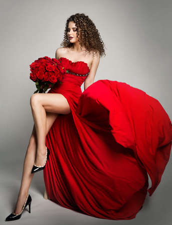 Beautiful Woman in Red Dress and Roses Flowers, Fashion Model Studio Portrait on White Banco de Imagens