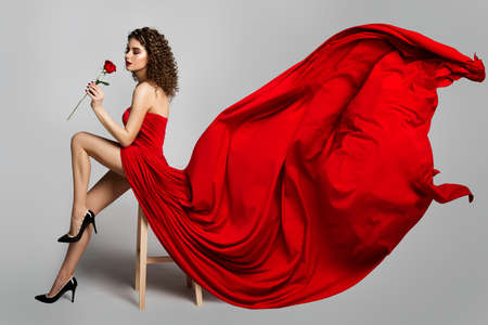 Beautiful Woman in Red Dress Smelling Roses Flowers, Fashion Model Studio Portrait on White, Flying Fluttering Cloth on Wind