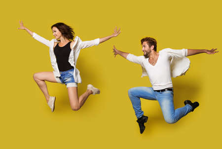 Jumping Couple, Full Length Profile Young People in Sport Dance, Isolated Yellow Background Banco de Imagens