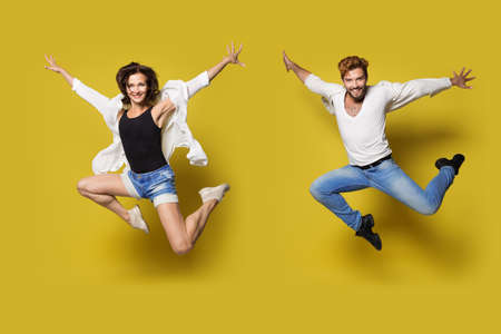 Jumping Couple, Full Length Young Happy People in Sport Dance, Isolated Yellow Background