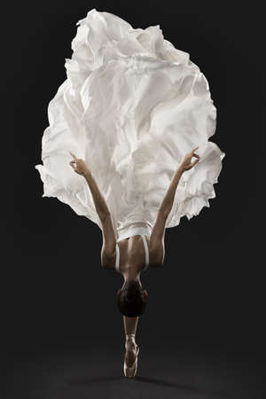 Ballerina Graceful Jump in White Silk Dress, Ballet Dancer Pointe Shoes in Fluttering Cloth, Black Background Banco de Imagens