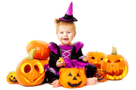 Halloween Child Girl Witch with Pumpkins in Carnival Costume, Holding Candy, Isolated White Background Banco de Imagens